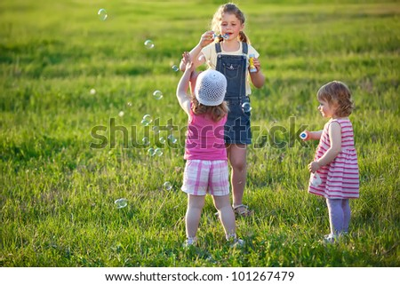 Happy children play with soap bubbles - stock photo