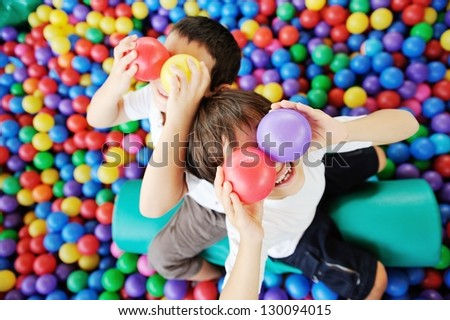Happy children playing and having fun at kindergarten with colorful balls on eyes - stock photo