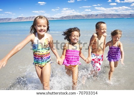 Happy Children playing and Splashing in the Ocean