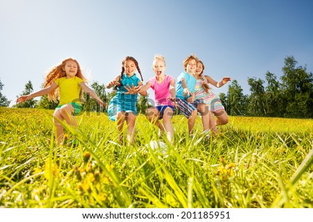 Happy children playing football in yellow meadow - stock photo