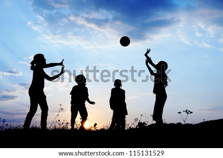 Happy children playing hand ball at sunset time - stock photo