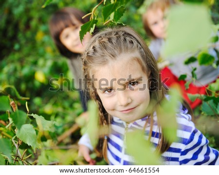 Happy children playing in nature, park, tree leaves - stock photo