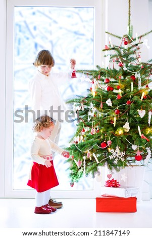 Happy children playing next to a Christmas tree. Beautiful curly toddler girl in a warm knitted dress helping her brother to decorate the Xmas tree standing next to a big window to a snowy garden - stock photo