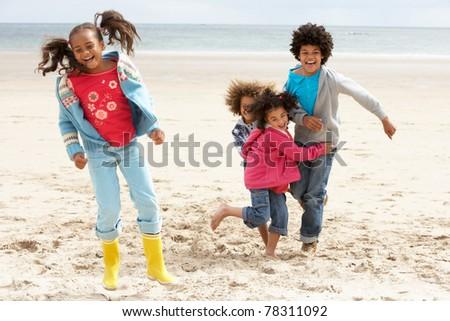 Happy children playing on beach - stock photo