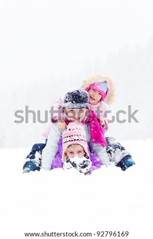 Happy children playing on snow - stock photo