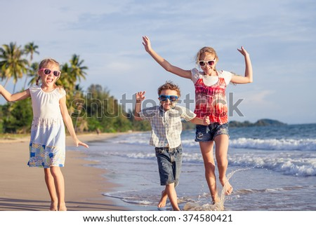 Happy children playing on the beach at the day time. Concept of friendly family. - stock photo