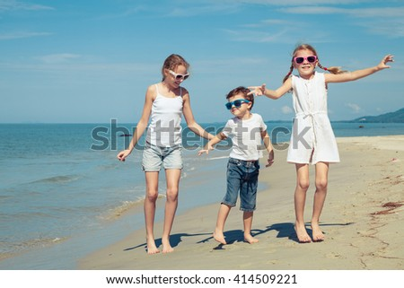 Happy children playing on the beach at the day time. Concept of friendly family.