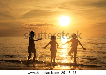 Happy children playing on the beach at the sunset time - stock photo