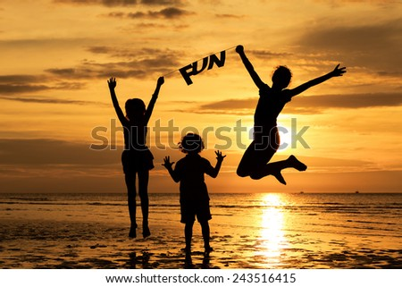 "Happy children playing on the beach at the sunset time. Children hold in the hands  inscription ""Fun"""