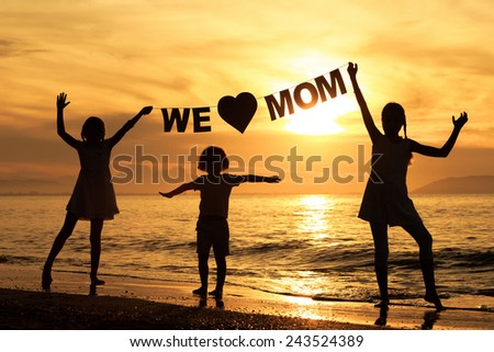 "Happy children playing on the beach at the sunset time. Children hold in the hands  inscription ""We love mom"". Concept of happy mother day. - stock photo"