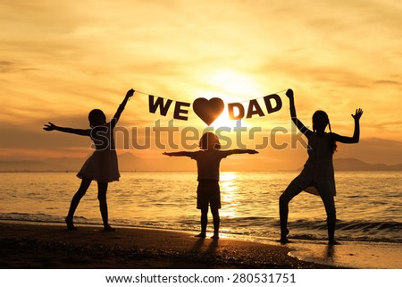 "Happy children playing on the beach at the sunset time. Children hold in the hands  inscription ""We love dad"" - stock photo"