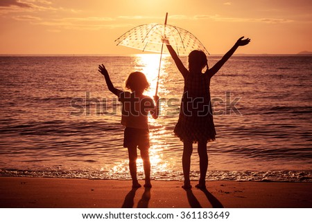 Happy children playing on the beach at the sunset time. Concept of happy friendly sister and brother. - stock photo