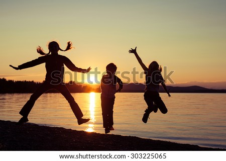 Happy children playing on the beach of lake at the sunset time