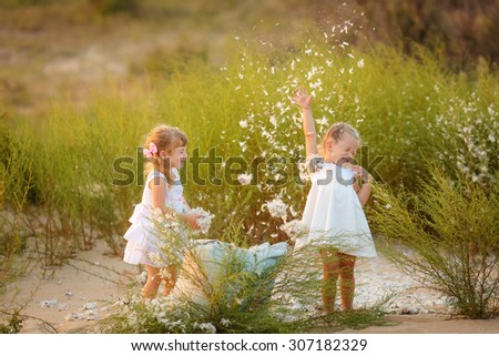 happy children playing on the beach. throwing feathers - stock photo