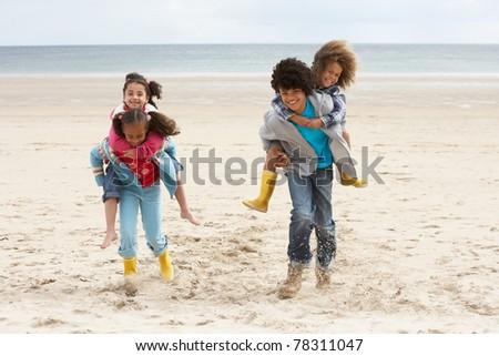 Happy children playing piggyback on beach - stock photo