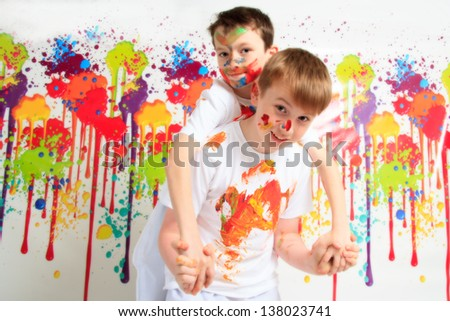 Happy children playing with paints - stock photo