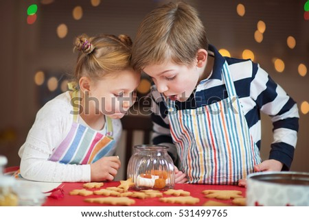 Happy children preparing cookies for Christmas and New Year at home