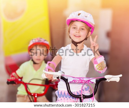 Happy children racing on bicycles, brother and sister organized sports competition, siblings with pleasure playing together, winner girl hand shows the sign of peace - stock photo