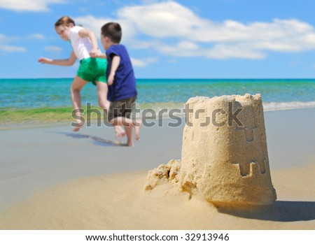 happy children running on beach by sand castle - stock photo