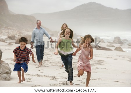 Happy children running on beach with parents walking in background - stock photo