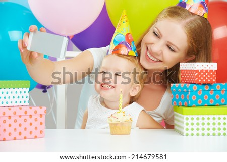 happy children's birthday. selfie. mother photographed  her daughter the birthday child with balloons, cake, gifts - stock photo