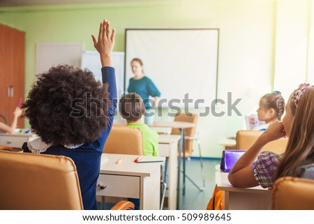 Happy children sitting in class and classmates in the background, doing schoolwork