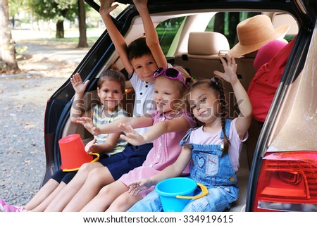 Happy children sitting on a car trunk