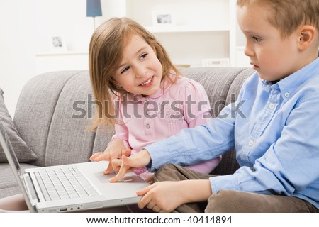 Happy children sitting on couch at home, browsing internet on laptop computer. Girl smiling at boy who focusing at screen.