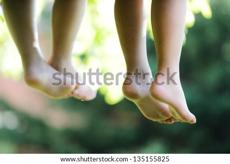 Happy children sitting on green grass outdoors in summer park - stock photo
