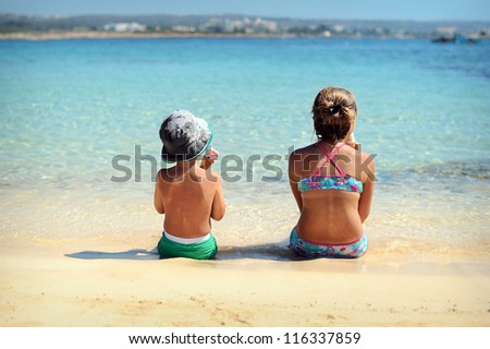 happy children sitting on the beach and eat ice cream. Sunny day by the sea.