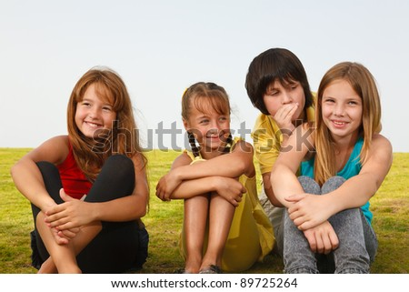 Happy children sitting on the grass and smiling