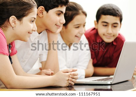 Happy children smiling and laughing in the classroom - stock photo