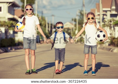 Happy children standing on the road at the day time - stock photo