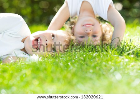 Happy children standing upside down on green grass. Boy and girl in spring park. Healthy lifestyles concept. - stock photo