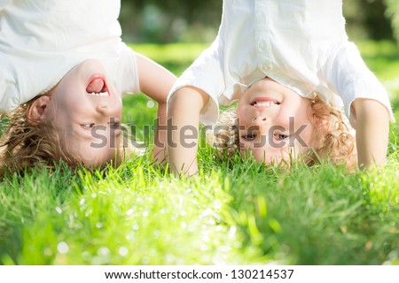 Happy children standing upside down on green grass in spring park. Healthy lifestyles concept.