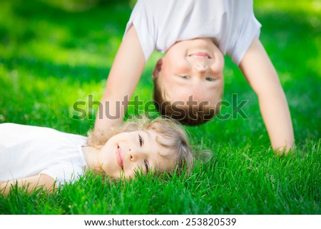 Happy children standing upside down on green grass. Smiling kids having fun in spring park. Healthy lifestyle concept - stock photo