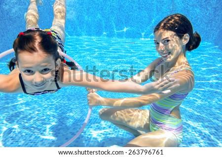Happy children swim in pool underwater, girls swimming, playing and having fun, kids water sport  - stock photo