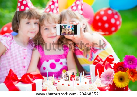 Happy children taking a selfie photo using the smartphone. Birthday party outdoors - stock photo