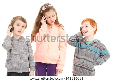 Happy children talking on mobile phones. Isolated on white.
