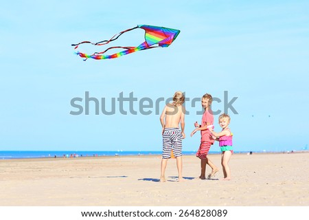 Happy children, teenager brothers with cute toddler sister playing together on the beach flying colorful kite - stock photo