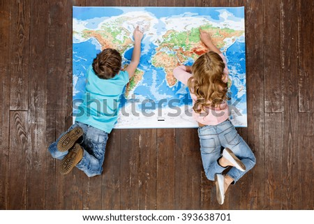 Happy children. Top view creative photo of little boy and girl on vintage brown wooden floor. Children lying on world map - stock photo