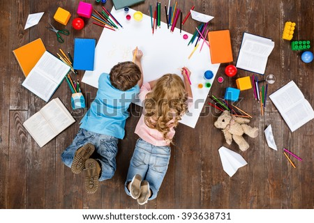 Happy children. Top view creative photo of little boy and girl on vintage brown wooden floor. Children lying near books and toys, and painting - stock photo