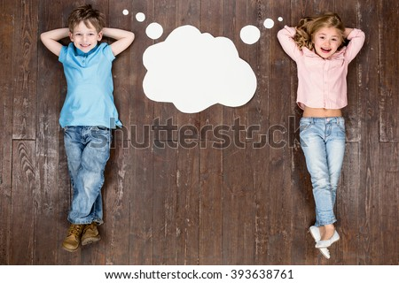 Happy children. Top view creative photo of little boy and girl on vintage brown wooden floor. Children lying near empty cloud with thoughts, looking at camera and smiling - stock photo