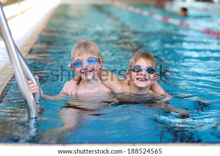 Happy children, twin teenagers boys in swimming goggles, having fun in the pool training before competition