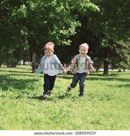 Happy children two boys brothers running together and having fun outdoors on the grass in summer day - stock photo