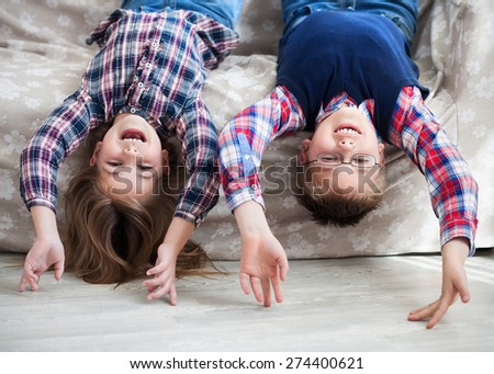 Happy children upside down on the sofa. Smiling kids having fun in living room.  Healthy lifestyle concept - stock photo