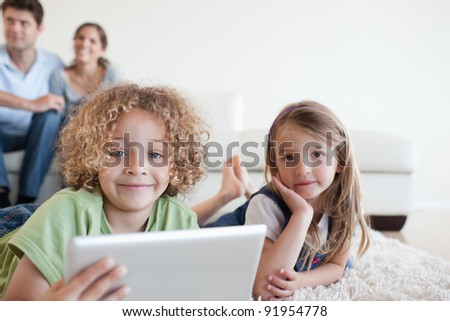 Happy children using a tablet computer while their happy parents are watching in their living room - stock photo