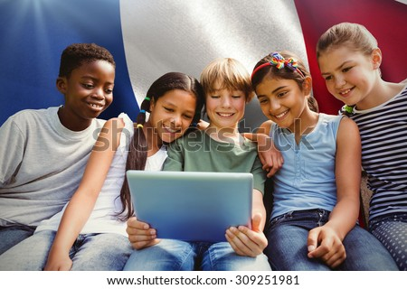 Happy children using digital tablet at park against digitally generated french national flag