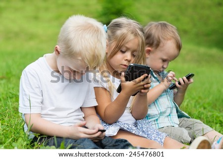 Happy children using smartphones sitting on the grass in the park. Brothers and sister. - stock photo