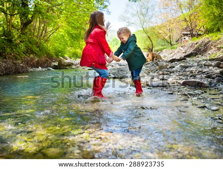Happy children wearing rain boots jumping into a mountain river
